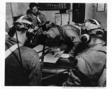 Soldiers on the radio and plotting table at Battery Chamberlin, cWWII.