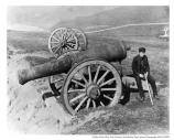 Man sitting on the Point Bonita Fog Cannon. The cannon was the first fog signal on the Pacific coast. Date Unknown.