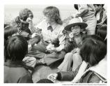 Ranger and youth looking at flowers, 1978. Child to left wearing ranger's hat and looking through magnifying glass.