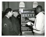 """Explaining some of the details of the new Post Office routine at the Presidio of San Francisco, is Serse Thompson, employee. Interested spectators are Sgt. WO Parks, and Col Perter J Lloyd, new Deputy Post Commander at the Presidio. 5 May 1952"""