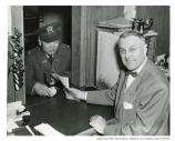William Toy in widow of post office with a man buying stamps, c. 1952.