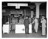 General Nelson M Walker, 23 August 1953 with the first shipload of repatriated Prisoners of War to reach the United States from Korea at the processing center in Warehouse D. Includes the Red Cross Canteen. Fort Mason. Credit: US Army Photograph.