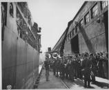 Troops loading ships at Fort Mason while a band plays on the docks, c1940s