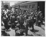 Coast Artillery troops exit trains at Fort Mason and prepare to load onto transports, cWWII.