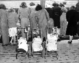 This 1945 photo shows a group of Army wives anxiously waiting to catch a glimpse of their returning husbands. Notice that the babies in the strollers have been identified with name tags.