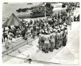 """WAC glee club from Camp Stoneman entertains the crowd."" Group of female service members gathered with aquatic vehicles in background, February 21, 1945"