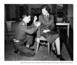 Male NCO sews stripes on a female NCO at Letterman, 6 March 1951