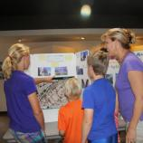 Student and family viewing exhibit panel.