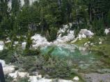 A turquoise green shallow cool water pool above the Bumpass Hell hydrothermal area.