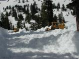 Frontloaders push snow into the path of the large rotary snowblowers while opening the road in April, 2008.