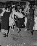 Before disembarking from bus at War Relocation Center, evacuees of Japanese descent are again examined by fellow evacuee medical staff. This baby (center) was found to have measles. The nurse is accompanying mother and child to Manzanar hospital.