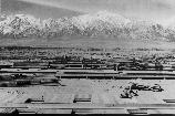 Construction begins at Manzanar, now a War Relocation Authority center for evacuees of Japanese ancestry, in Owens Valley, flanked by the High Sierras and Mt. Whitney, loftiest peak in the United States. (note: mountain behind Manzanar is actually Mt. Williamson)