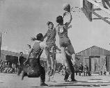Basket ball games are part of the regular scheduled recrational events, shich help fill out the lives of residents in relocation centers. These boys are participating in a nip and tuck game, which frequently brought the spectators to their feet.