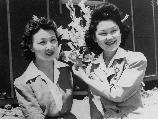 Nancy Kaweshima (left), and Emiko Hino, both from Los Angeles, arrange paper flowers for one of many art exhibits at Manzanar, a War Relocation Authority center where evacuees of Japanese ancestry will spend the duration.