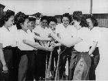 Members of the Chick-a-dee soft ball team from Los Angeles choose sides for a practice game at Manzanar, where, since evacuation, the girls have kept their team intact. The squad leaders, with hands on bat, are: Ritsuko Masuda (left), and Marion Fujii.