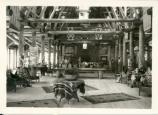 Black and white photo of log-constructed lodge with guests sitting in chairs.