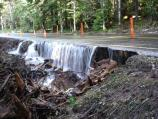 Ten days after the storm, Kautz Creek continues to flow across and undermine the park road.