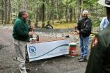 Congressmen Norm Dicks and Dave Reichert demonstrate a cross-cut saw in the Longmire Campground, base camp for a Flood Recovery Corps led by the Student Conservation Association (SCA). Mount Rainier superintendent Dave Uberuaga looks on.