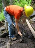 A volunteer helps repair damage to the Comet Falls Trail, as part of an SCA-led work party.