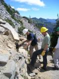 Volunteers help rebuild a rock wall along the trail at Sunrise, in Mount Rainier National Park, under the direction of SCA crew leaders.