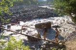 Volunteer backcountry patrol rangers cross a log bridge over the Mowich River