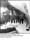 Taken onboard the Star of Alaska in 1919. The ship is in heavy seas and some crew members are shown here wearing their oilskins standing in knee deep water as water rushes onto the deck of the ship.