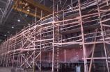 The wooden hull of a large vessel covered with scaffolding.