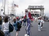 A stilt walker, dressed as Uncle Sam, shakes hands with a woman on Hyde St. Pier.