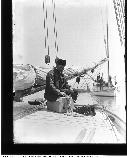 A man sitting on the deck of a schooner with a small dog in a little house next to a miniature cannon.