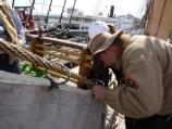 Volunteer tying a sail onto a stay using a metal hank, or ring.