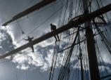 Two park rangers stand on a foot rope above the deck of a sailing ship holding onto a spar.