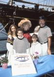 A costumed set of parents and their three children pose behind CA THAYER's anniversary cake.