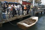 Students from Downtown High School in San Francisco, CA, celebrate the completion of a boat building class. They built a small wooden sailboat called a Pelican.