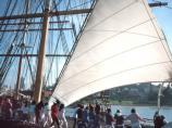 Visitors join in and help raise the staysail on Balclutha.