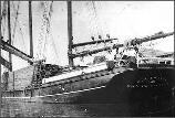 A view of the port side and stern end of the lumber schooner CA Thayer, with a load of lumber on her deck. F1.6376