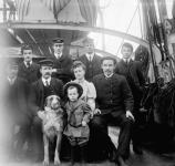 Main deck of the sailing ship BALMORAL, built in 1892. Captain and Mrs. J. E. Roop, their son and dog, surrounded by officers and crew members in Tacoma, WA.