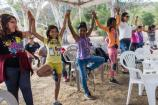Youth hold their hands up as they practice a balancing yoga pose