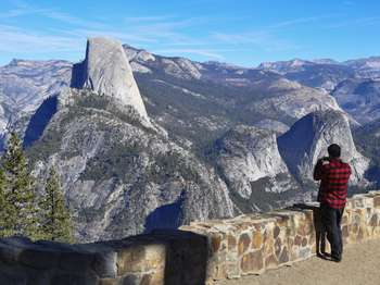 A person takes a photo of the scenery, which includes Half Dome and surrounding rock formations, on his cell phone.