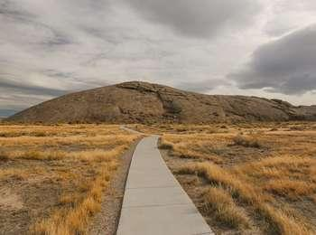 Pathway leading through grass and sagebrush plains to a larger dome shaped natural rock formation