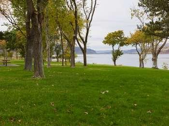 Park with picnic table, grass lawn, trees, and the Columbia River