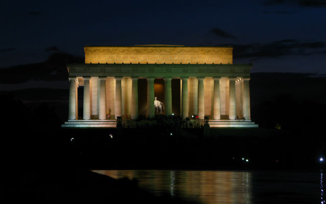A dark dusky sky behind the glowing Lincoln Memorial, which sits in front of a reflecting pool.