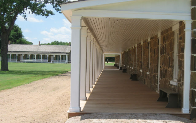 a dirt road passes in front of long stone building with white porch columns