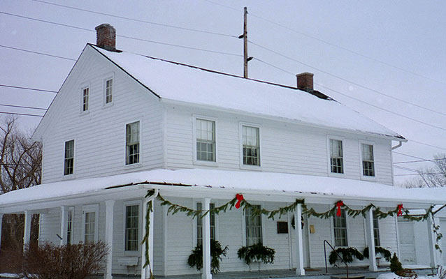 Harriet Tubman Home for the Aged in the winter. White snow makes the white house look fluffy.