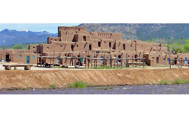 Multistory Pueblo building made of adobe on a riverbank.