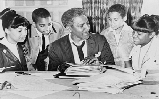 Bayard Rustin sitting with 4 children. Black and white photo