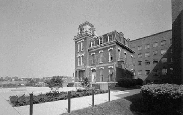 Black and white photograph of Howard Hall with modern building behind it