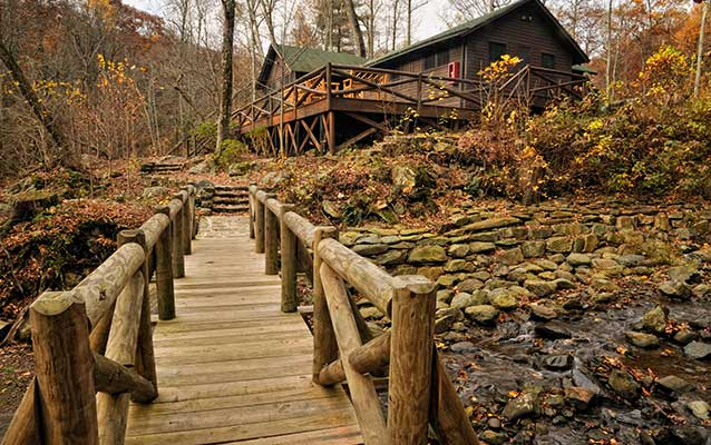 A rustic log footbridge leads to a large brown cabin in the woods.