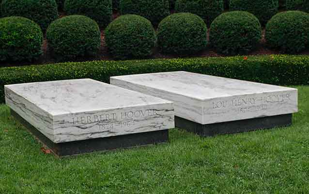 A president's and first lady's graves are marked with two white marble slabs.