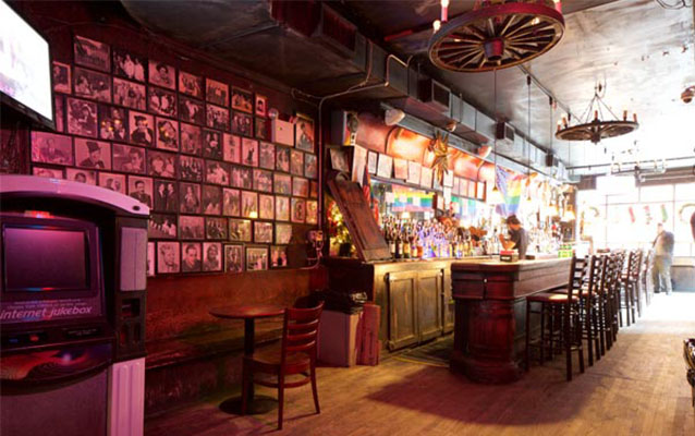 Interior view of Julius Bar. Bar with stools; several images on the wall.
