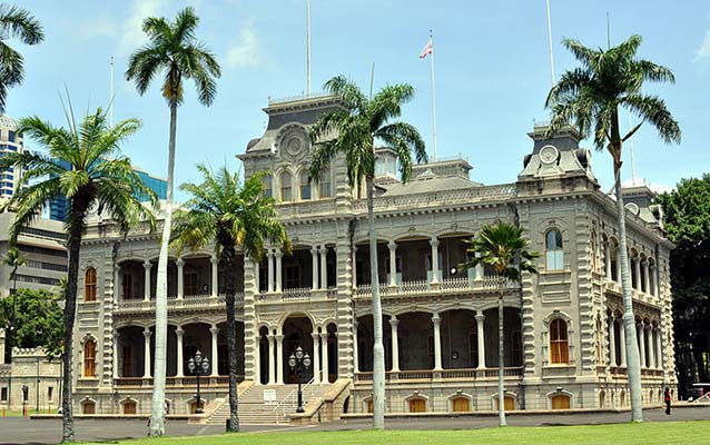 Exterior of 'Iolani Palace, Honolulu with lawn and pine trees in front